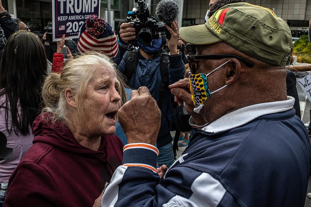 """A supporter of President Donald Trump (left) and another protester argue Thursday during a rally outside a convention center in Detroit, where ballots were being counted. Some pro-Trump protesters held signs that read, """"Stop the steal"""" and """"Stop the cheat."""" (The New York Times/Bryan Denton)"""
