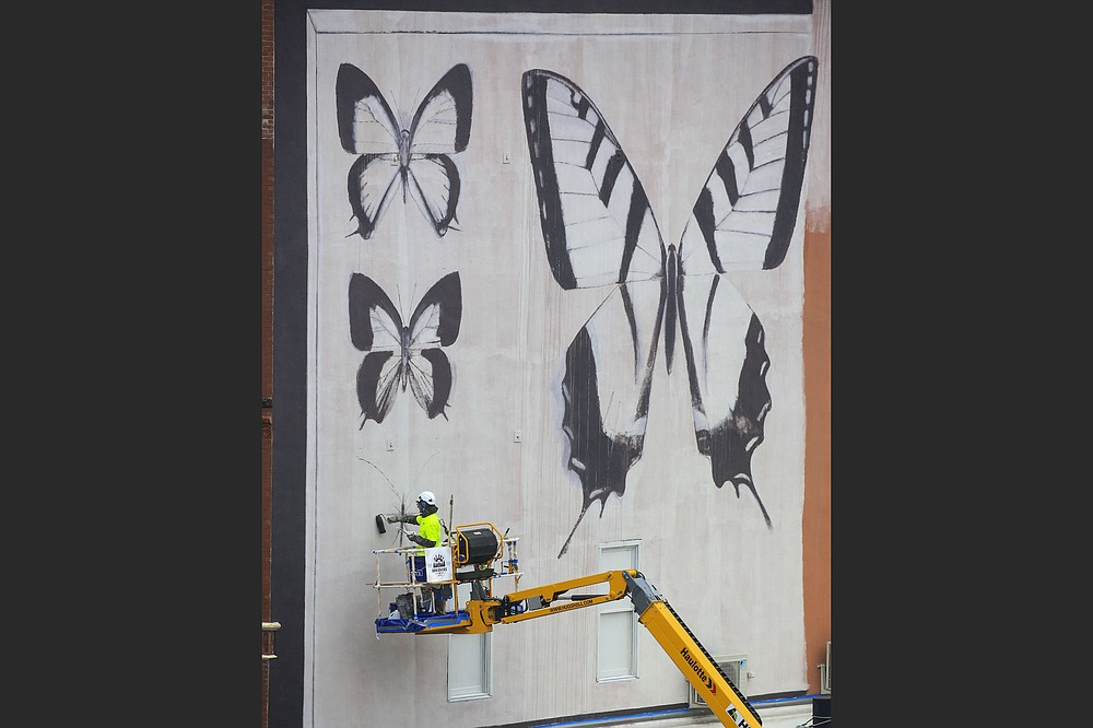 French artist Youri Cansell starts his mural, depicting moths and butterflies, last month on the east wall of the River Market's Ottenheimer Market Hall, 400 President Clinton Ave., Little Rock. The completed mural will be officially unveiled during Second Friday Art Night, 5-8 p.m. Friday. (Arkansas Democrat-Gazette/Staton Briedenthal)