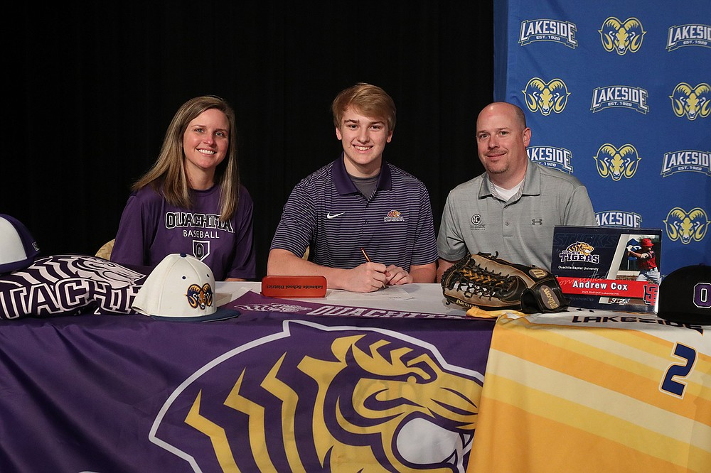 Andrew Cox, center, is joined by his mother Betsy, left, and father Robbie Friday after signing a letter of intent to play baseball at Ouachita Baptist University. - Photo by Richard Rasmussen of The Sentinel-Record