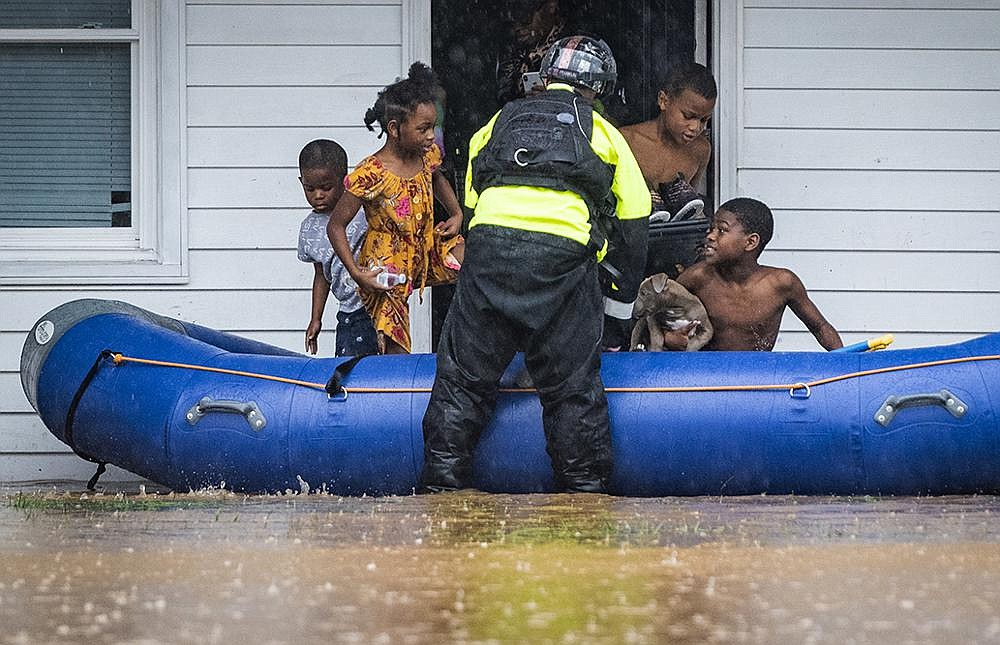 A firefighter from the Winston-Salem, N.C., Fire Department helps children into a raft Thursday at an apartment complex that was flooded by heavy rain moving ahead of Tropical Storm Eta. At a nearby campground, three people were killed and two more were missing when the South Yadkin River flooded. More photos at arkansasonline.com/1113nc/. Video at arkansasonline.com/1113flooding/. (AP/The Winston-Salem Journal/Andrew Dye)