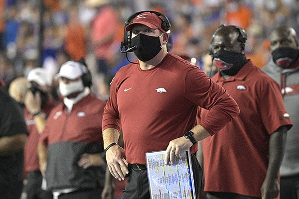 Arkansas defensive coordinator Barry Odom, center, watches a stadium video monitor after Florida scored a touchdown during the first half of an NCAA college football game, Saturday, Nov. 14, 2020, in Gainesville, Fla. Odom was acting as the Razorbacks' interim head coach during the game. (AP Photo/Phelan M. Ebenhack)