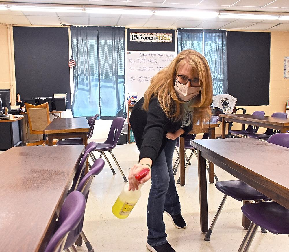Amy Baker, an English teacher, sanitizes desks and chairs between classes in her room in Concord. The Concord School District, like one in every five Arkansas school districts, has neither the funds nor nearby providers for student mental health care, so faculty and staff members are getting trained to spot warning signs and take action. (Arkansas Democrat-Gazette/Staci Vandagriff)