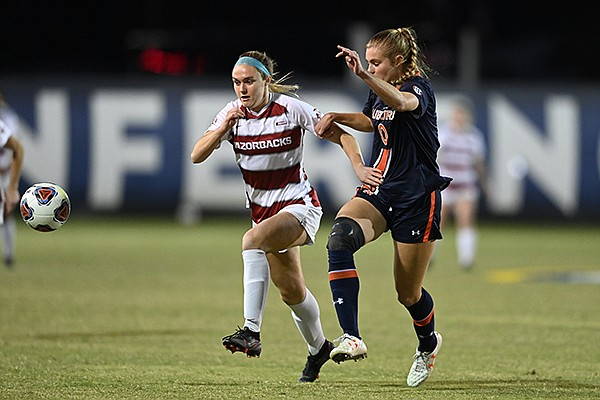 Arkansas' Anna Podojil (left) pursues a ball against Auburn's Madeline Moore during an SEC Tournament game Tuesday, Nov. 17, 2020, in Orange Beach, Ala.