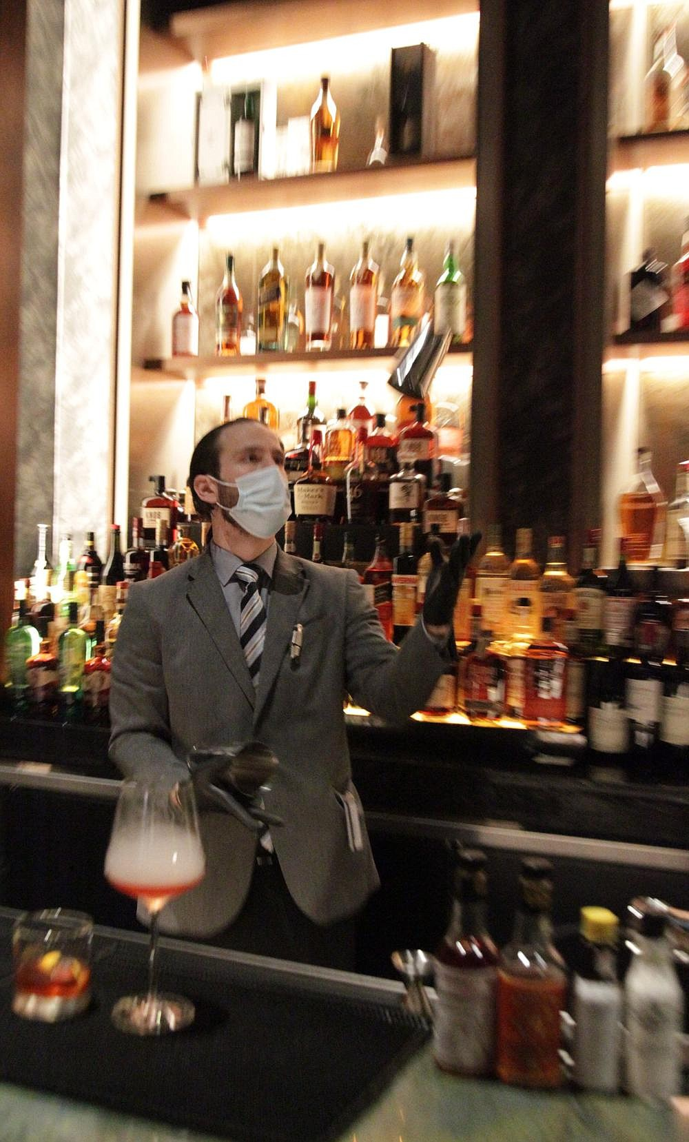 Mark Lopez, Red Oak Steakhouse sommelier, demonstrates his prowess behind the bar as he prepares drinks Friday afternoon. Food and bar service will close nightly at 11 p.m. following a request by the Arkansas Department of Health, but individual drink service to patrons on the casino gambling floor will continue until the casino closes at 2 a.m. 