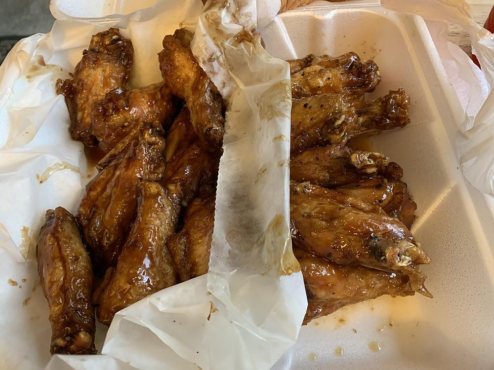 We split our order of 16 wings from Jacob's Wings & Grill into two sauce flavors: teriyaki (left) and lemon pepper. (Arkansas Democrat-Gazeette/Eric E. Harrison)