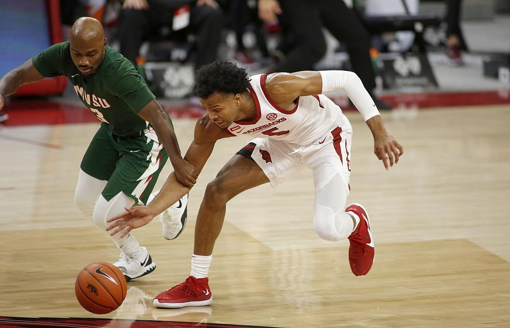 Arkansas' Moses Moody (right) steals the ball from Mississippi Valley State's Caleb Hunter during  the Razorbacks' season-opening victory Wednesday night at Walton Arena in Fayetteville.  (NWA Democrat-Gazette/David Gottschalk)