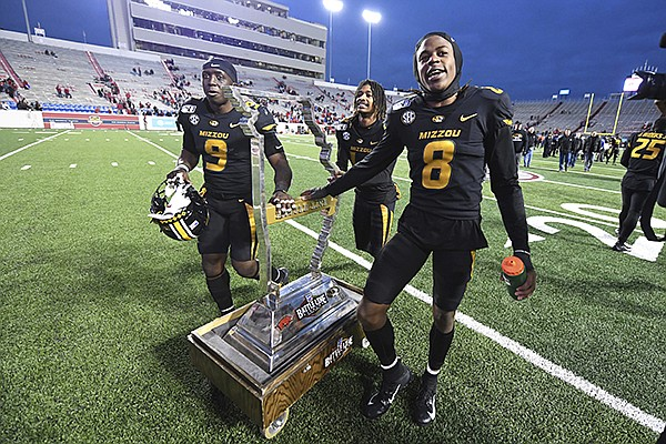 Missouri's Tyree Gillespie (9), Adam Sparks (14) and Jarvis Ware (8) celebrate as they wheel off the Battle Line trophy after Missouri defeated Arkansas 24-14 during an NCAA college football game Friday, Nov. 29, 2019, in Little Rock. (AP Photo/Michael Woods)