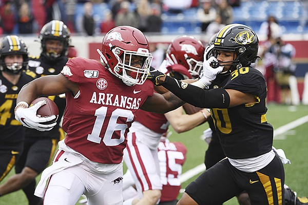 Arkansas receiver Treylon Burks gives Missouri defender Zion Sales a stiff arm as he returns a kick off against during an NCAA college football game, Friday, Nov. 29, 2019 in Little Rock. (AP Photo/Michael Woods)