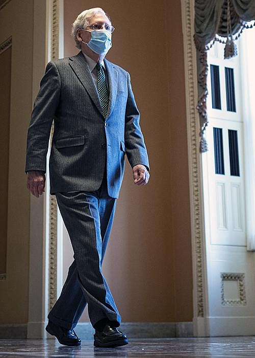 "Senate Majority Leader Mitch McConnell walks to the Senate floor Thursday. ""Compromise is within reach. We know where we agree. We can do this,"" McConnell said without disclosing his position on a bipartisan relief bill.