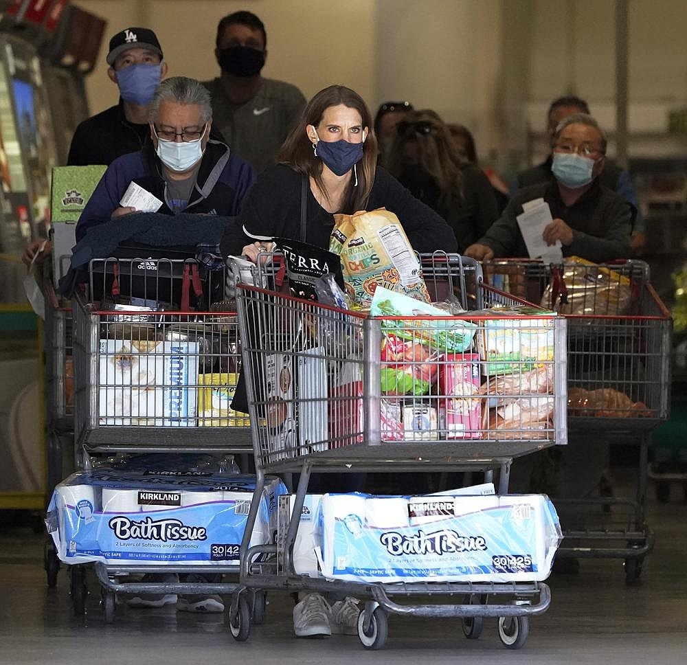 Shoppers with laden carts exit a Costco store in Santa Clarita, Calif., on Friday as California is on the brink of a new stay-at-home order that would close businesses and curb travel in regions where hospitals could be overwhelmed by coronavirus patients. More photos at arkansasonline.com/125covid/.