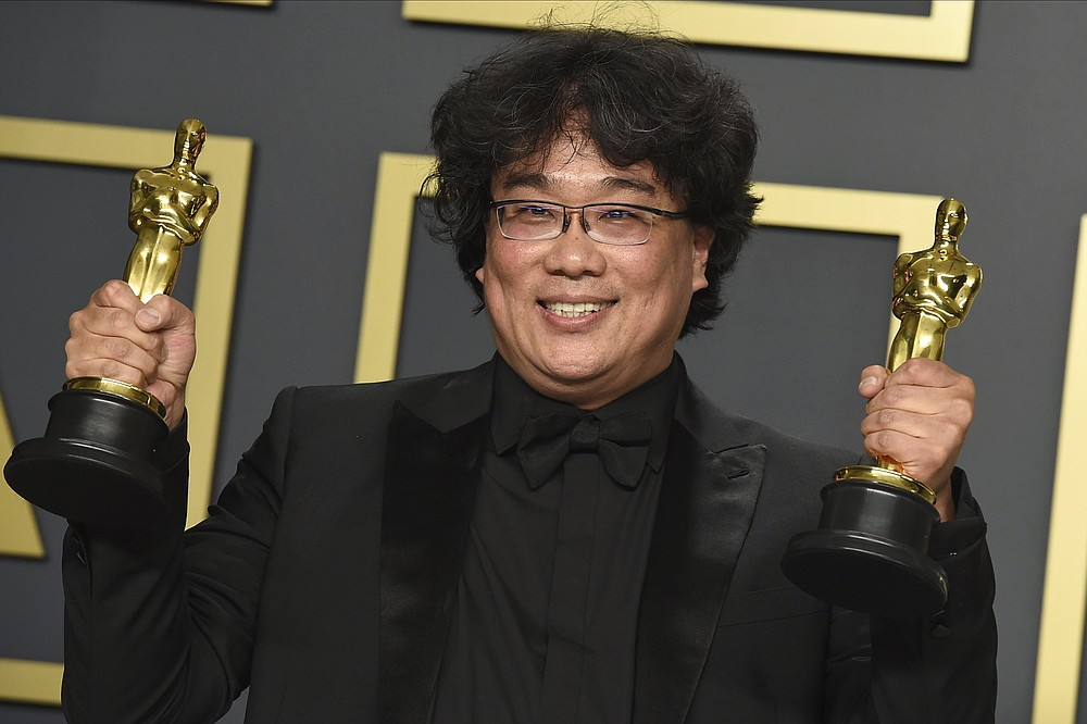 """Bong Joon Ho poses in South Korea with the awards for best director for """"Parasite"""" and for best international feature film for """"Parasite"""" at the Oscars in Los Angeles on Feb. 9. Bong Joon Ho won four awards, including one for best original screenplay and best picture. (Jordan Strauss/Invision/AP file)"""