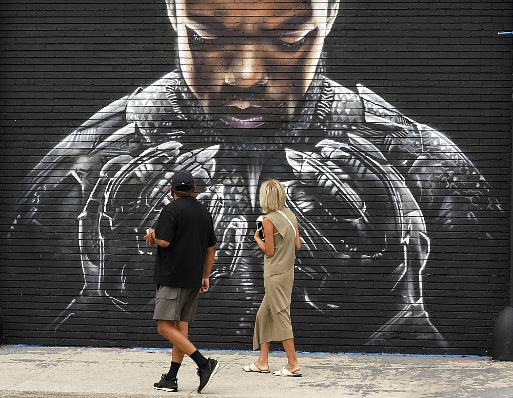 """Pedestrians look up at a mural by artist Shane Grammer of late actor Chadwick Boseman's character T'Challa from the 2018 film """"Black Panther,"""" on Sept. 8 in Los Angeles. Boseman died of colon cancer Aug. 28 at age 43. The world mourned the actor who, like many of his characters, radiated a regal sense of dignity. (AP Photo/Chris Pizzello, File)"""