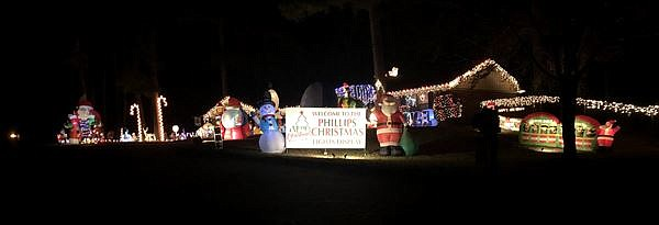 The Phillips family Christmas display includes multiple Santas and bright lights.