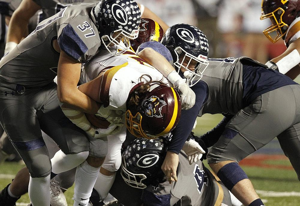 Greenwood defenders Daniel Langley (left) and Angel Hernandez tackle Lake Hamilton quarterback Grant Bearden during the Class 6A state championship game Dec. 5. The Bulldogs won 49-24 for their third state title in four seasons and 10th since 2000. (Arkansas Democrat-Gazette/Thomas Metthe)