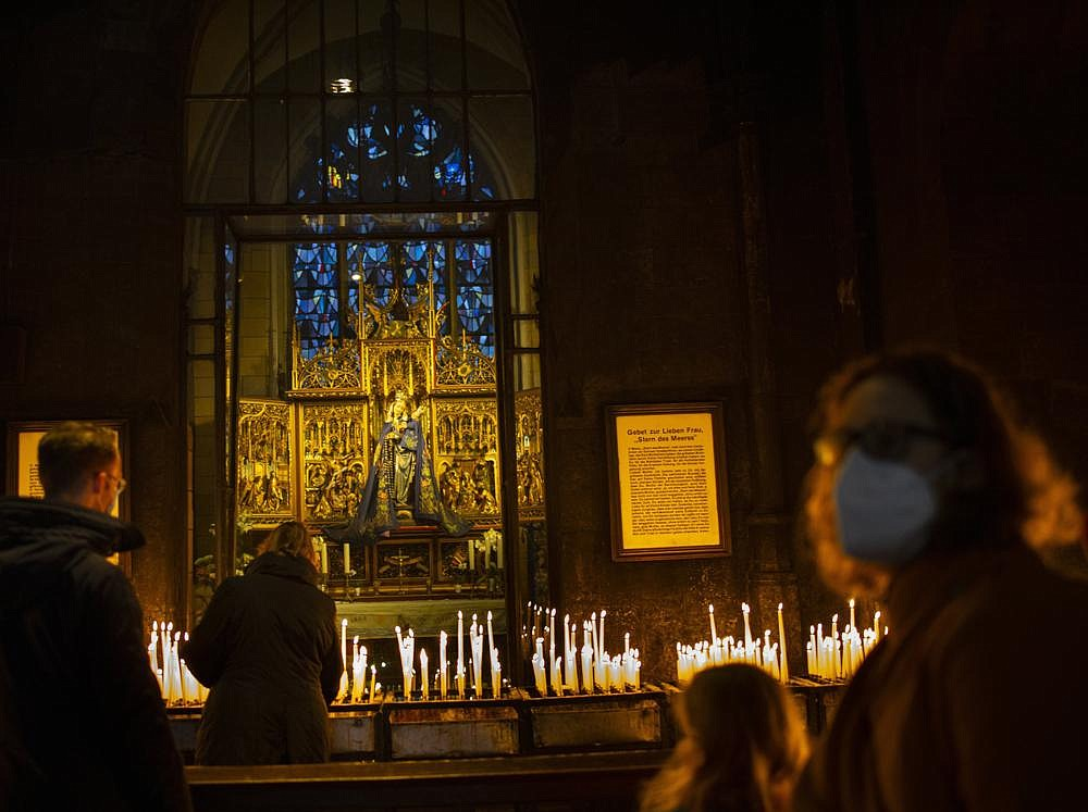 Worshippers offer prayers and light candles on Christmas Day at the Basilica of Our Lady in Maastricht, Netherlands. (AP/Peter Dejong)