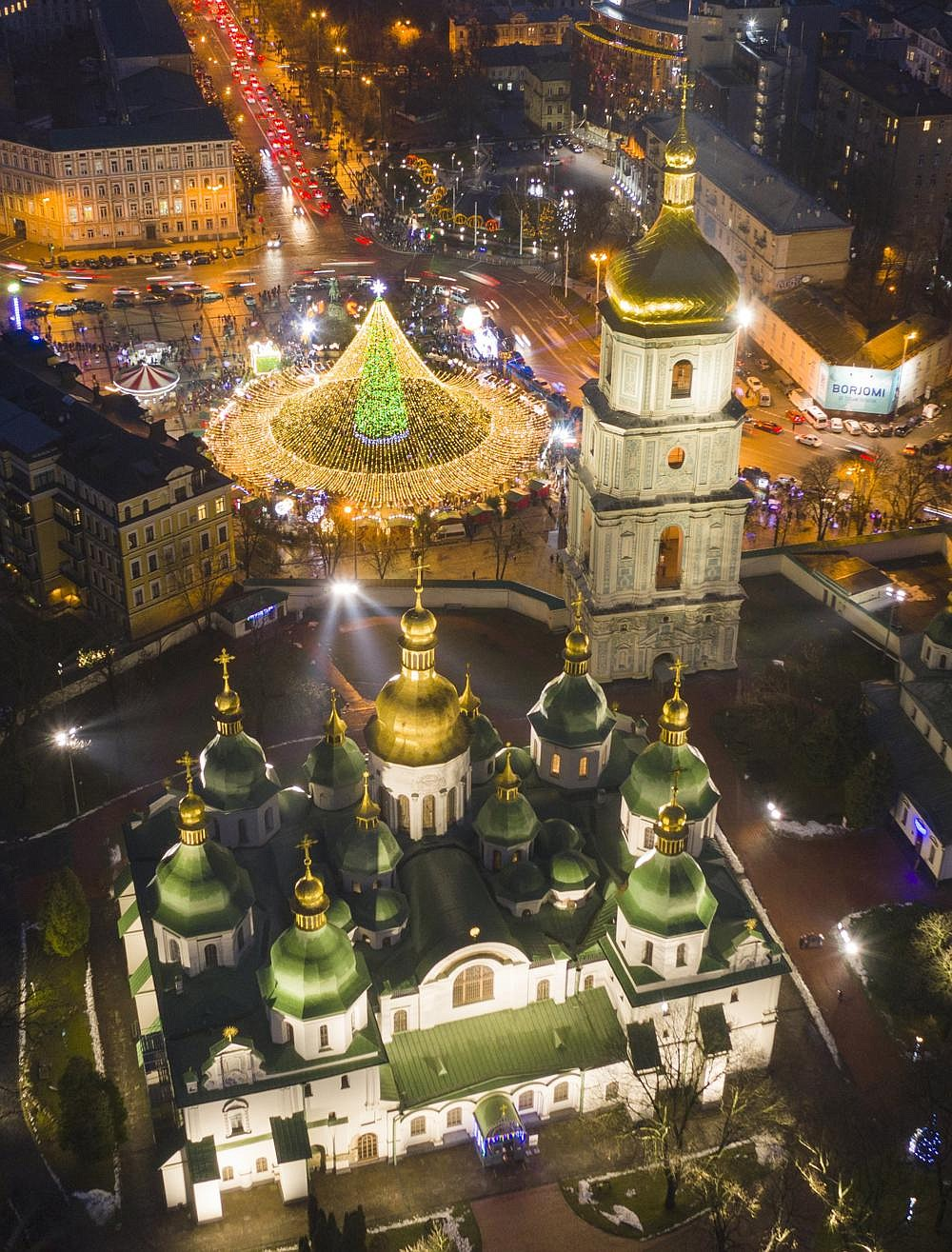 The Christmas tree encased in lights shines Friday behind the St. Sofia Cathedral in Kyiv, Ukraine. (AP/Efrem Lukatsky)