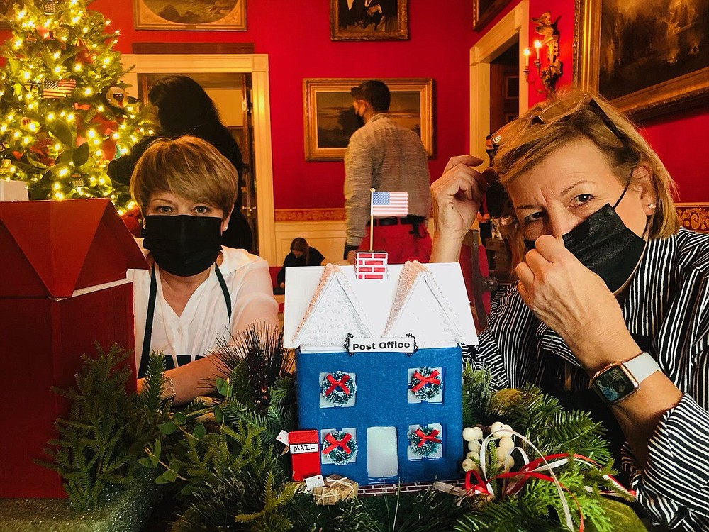 Julie Walters from South Carolina, left, sits with Liz Bullock, right, as they decorate the Red Room in the White House. This year the room was decorated to honor first responders and essential workers of 2020. (Contributed)