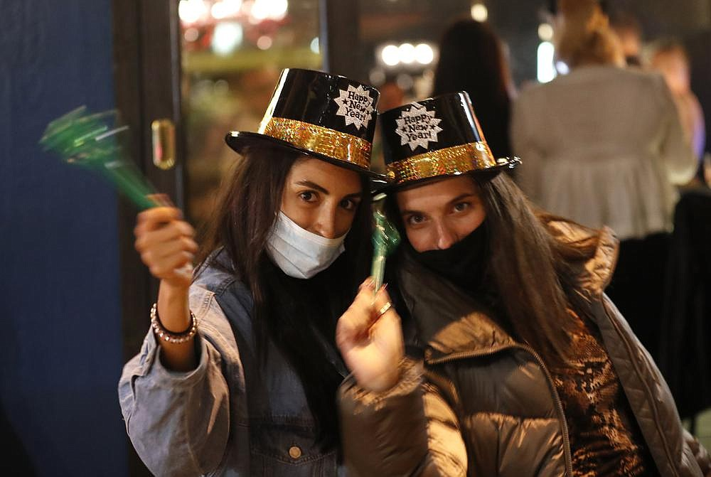 Lebanese women, wearing masks to help prevent spread of the coronavirus, celebrate the New Year outside a pub Thursday in Beirut. (AP/Hussein Malla)