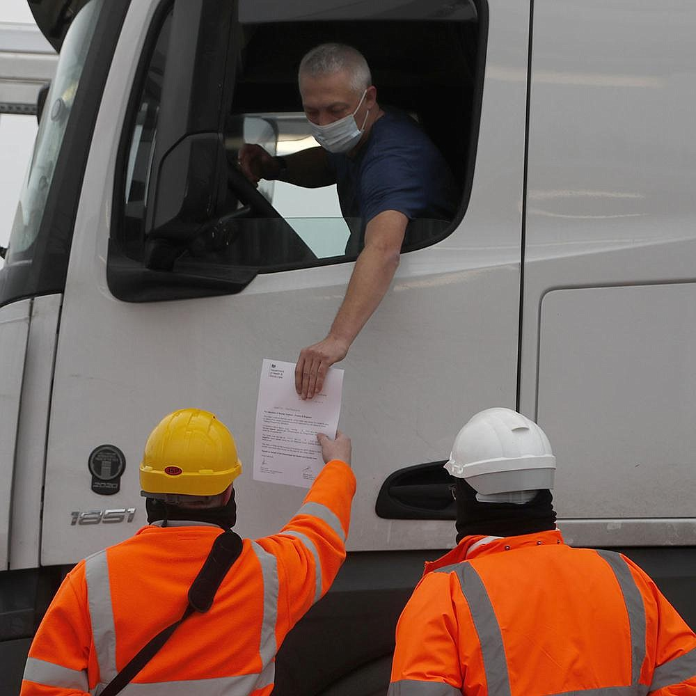 A truck driver's documents are checked Friday at the Eurotunnel in Folkestone, England, that connects Great Britain to France. (AP/Frank Augstein)