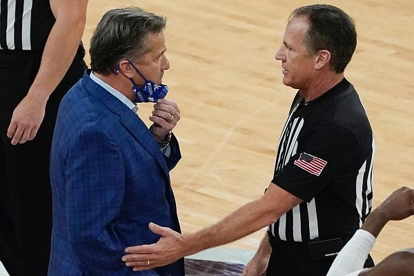Kentucky head coach John Calipari, left, confers with an official after being tossed out of an NCAA college basketball game against Mississippi State during the second half in Starkville, Miss., Saturday, Jan. 2, 2021. (AP Photo/Rogelio V. Solis)