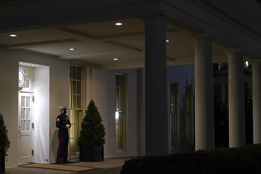 A Marine stands Thursday, Jan. 7, 2021, outside the entrance to the West Wing of the White House, signifying President Donald Trump is in the Oval Office in Washington.