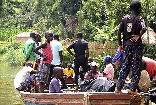 Children gather around a wooden boat conveying two bodies Wednesday in Mukwija in Eastern Congo, after a motorized boat capsized overnight on Lake Kivu, officials said. (AP/Justin Kabumba)