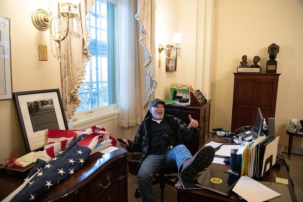 """Richard """"Bigo"""" Barnett, 60, who had his picture taken Wednesday while sitting in House Speaker Nancy Pelosi's office after he and other protesters stormed the U.S. Capitol, is a resident of Benton County, the mayor of Gravette and a county justice of the peace confirmed. (Special to the Arkansas Democrat Gazette/AFP via Getty Images/Saul Loeb)"""