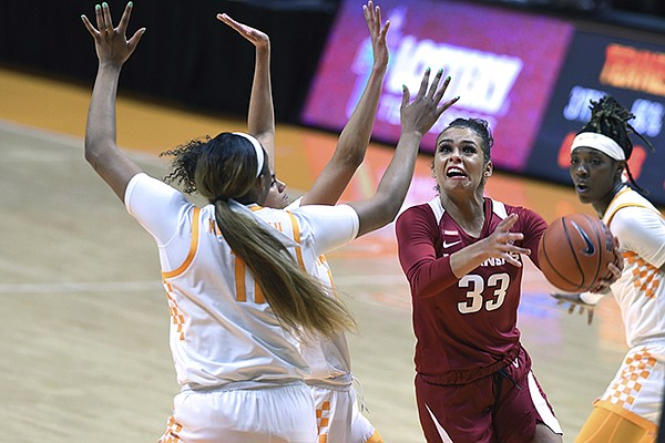 Arkansas' Chelsea Dungee (33) scores on a drive with Tennessee's Rae Burrell and Kasiyahna Kushkituah (11) defending during an NCAA college basketball game Thursday, Jan. 7, 2021, in Knoxville Tenn. (Scott Keller/The Daily Times via AP)