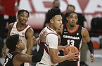 Arkansas forward Jaylin Williams (center) is defended by Georgia guard Savhir Wheeler (2) during a game Saturday, Jan. 9, 2021, in Fayetteville.