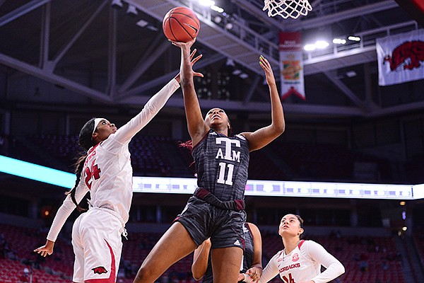 Texas A&M's Kayla Wells (11) shoots over Arkansas' Taylah Thomas (24) during a game Sunday, Jan. 10, 2021, in Fayetteville.