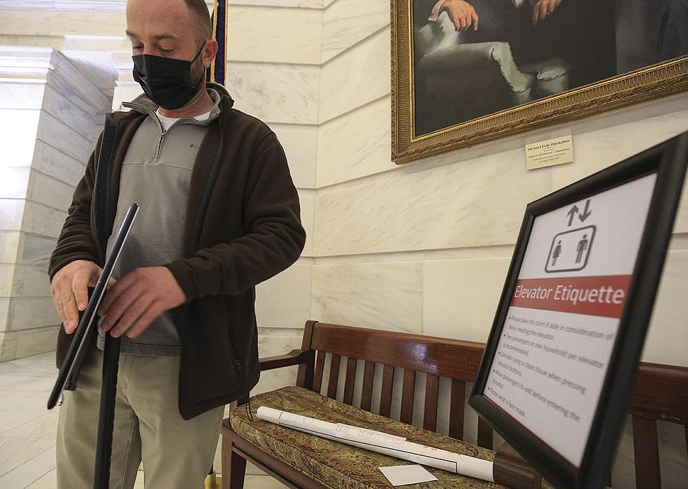 Brent Stamp, director of facilities for the state Capitol, assembles signs Friday to inform visitors about elevator etiquette ahead of the start of the legislative session.(Arkansas Democrat-Gazette/Staton Breidenthal)