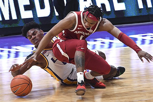 LSU forward Mwani Wilkinson, left, and Arkansas guard JD Notae (1) vie for the ball during the first half of an NCAA college basketball game Wednesday, Jan. 13, 2021, in Baton Rouge, La. (Hilary Scheinuk/The Advocate via AP)