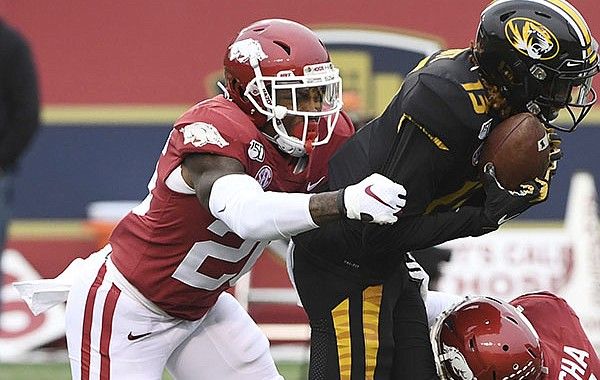 Arkansas defensive back Micahh Smith (left) tackles Missouri receiver Kam Scott during a game Friday, Nov. 29, 2019, in Little Rock. (AP Photo/Michael Woods)