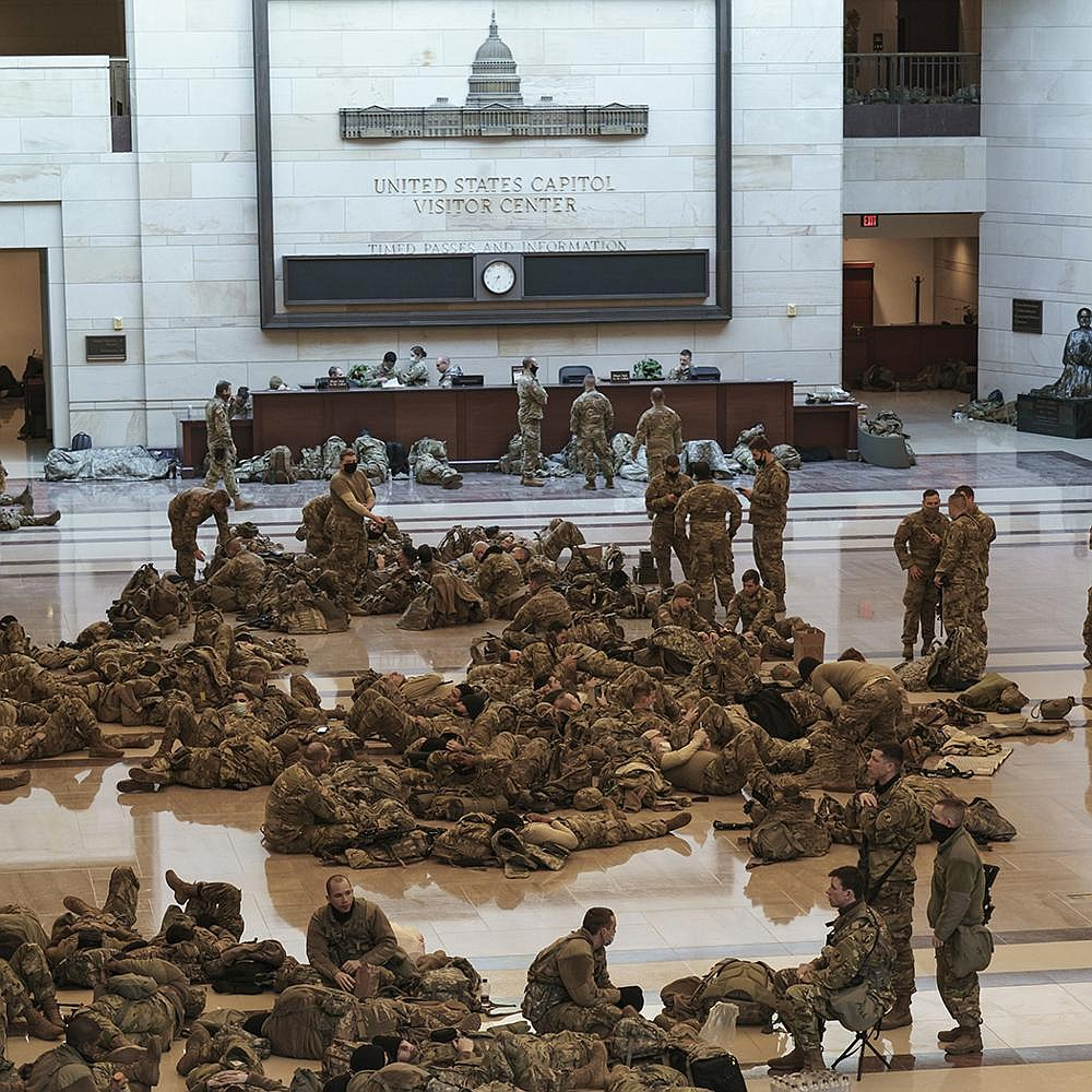 National Guard troops rest inside the U.S. Capitol on Wednesday while providing extra security for the House impeachment vote just a week after a mob stormed the building. Officials said more than 20,000 Guardsmen could be on duty for Inauguration Day security.