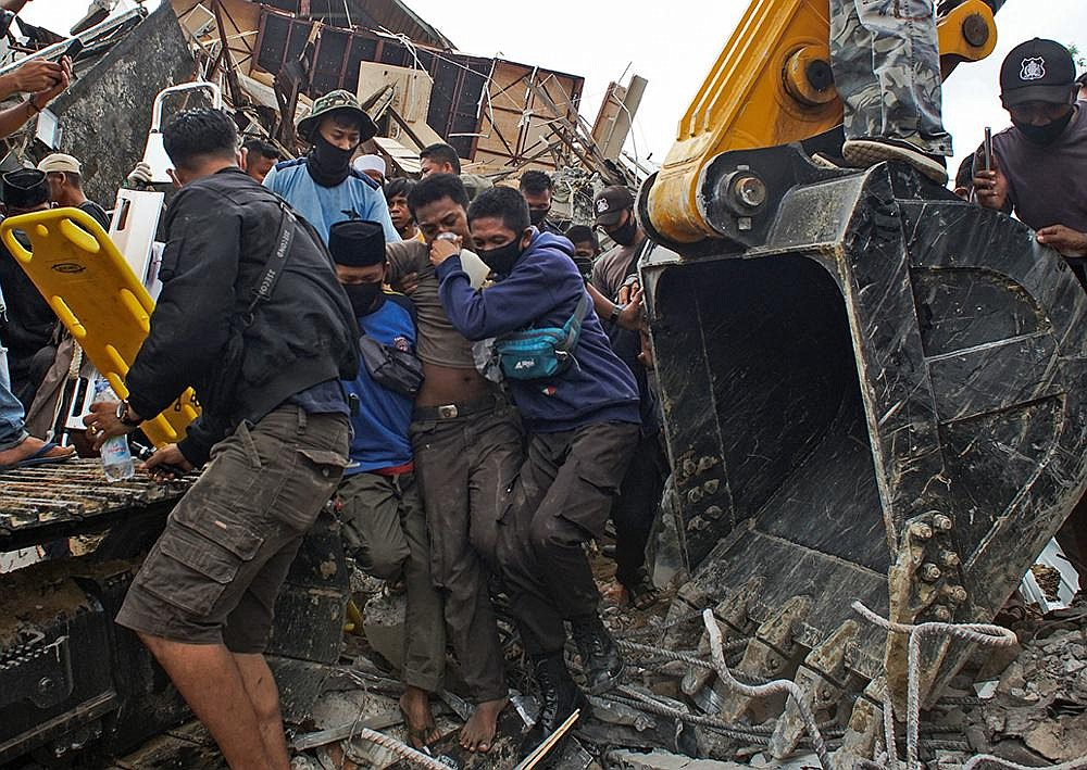 Rescuers assist a survivor pulled from the ruin of a government building that collapsed during an earthquake early Friday in Mamuju, Indonesia. The quake that shook Indonesia's Sulawesi island toppled buildings, triggered landslides and killed scores of people. More photos at arkansasonline.com/116sulawesi/. (AP/Azhari Surahman)
