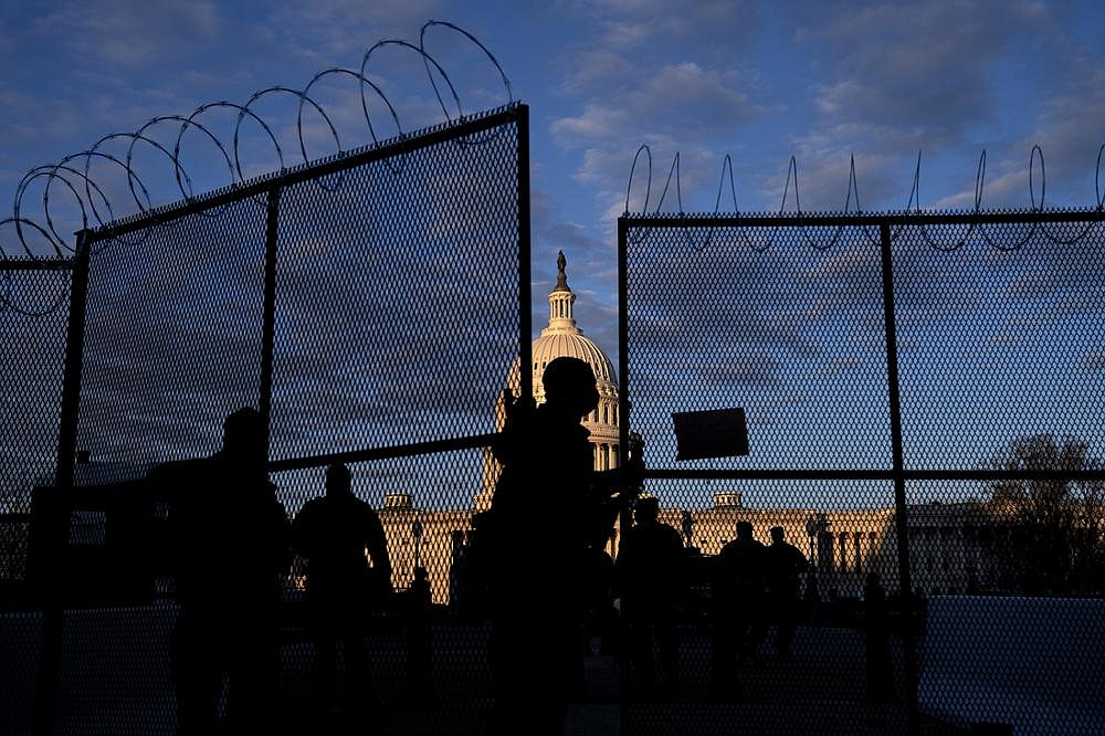 A member of the National Guard closes security fencing Saturday outside the U.S. Capitol.