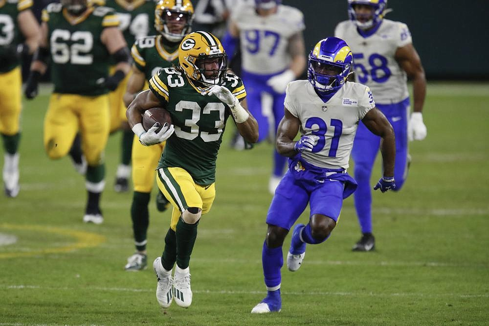 Green Bay Packers running back Aaron Jones (33) runs the ball as Los Angeles Rams cornerback Darious Williams attempts to catch him Saturday night at Lambeau Field in Green Bay, Wis. Jones rushed for 99 yards and a touchdown on 14 carries to help the Packers to a 32-18 victory over the Rams. (AP/Matt Ludtke)