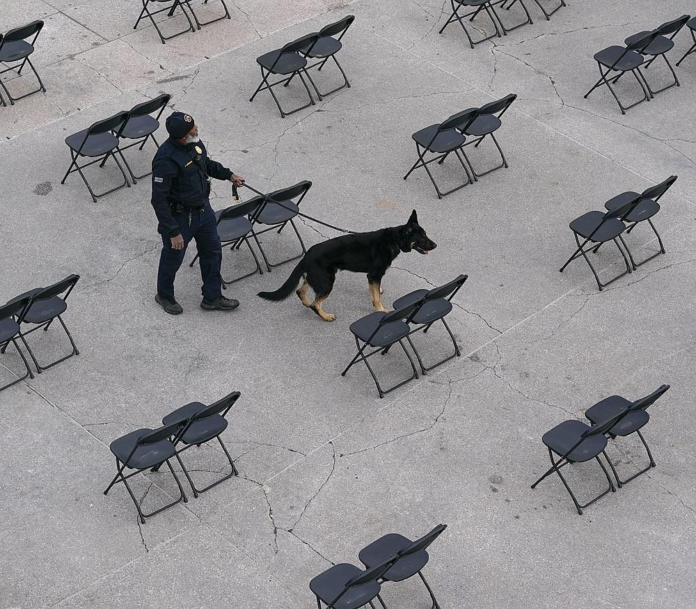 A Capitol Police officer and his dog sweep a spectator seating area Saturday outside the U.S. Capitol as preparations take place for President-elect Joe Biden's inauguration ceremony Wednesday. More photos at arkansasonline.com/117dcguard/.