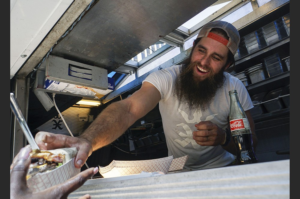 Kyle Pounders hands a burger to an Excaliburger customer at Capitol Avenue and Main Street in downtown Little Rock in April 2018. (Democrat-Gazette file photo)