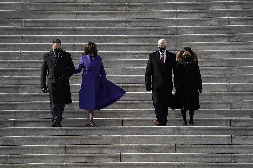 Vice President Kalama Harris (second from left) and her husband, Doug Emhoff, escort former Vice President Mike Pence and his wife, Karen, down the Capitol steps Wednesday after inauguration ceremonies. (The New York Times/Amr Alfiky)