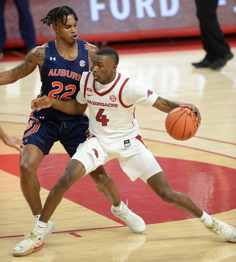 Arkansas freshman guard Davonte Davis dribbles against Auburn's Allen Flanigan during the Razorbacks' victory Wednesday night. Arkansas trailed by 19 points in the game,and it is believed to be the Hogs' largest comeback at Walton Arena.