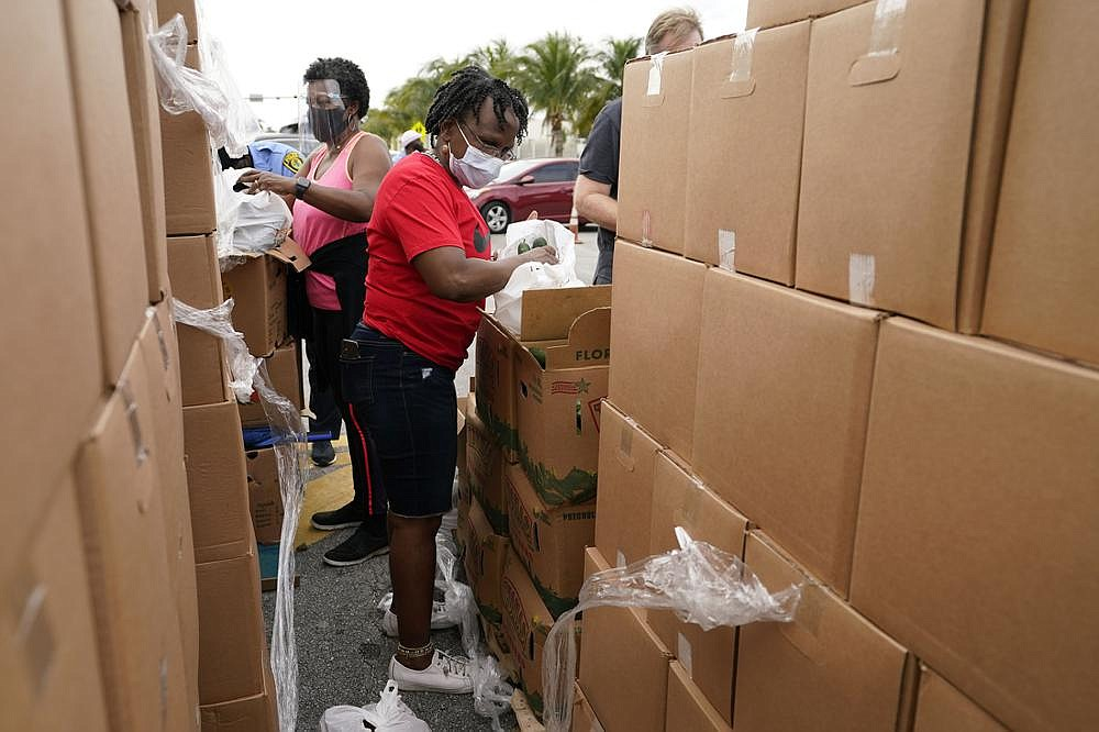 Sharon Smith-Butler (right) bags produce Thursday as she works with other volunteers at a food distribution site sponsored by Feeding South Florida in Florida City, Fla. The effort was to help people affected economically by the pandemic and others in need. (AP/Lynne Sladky)
