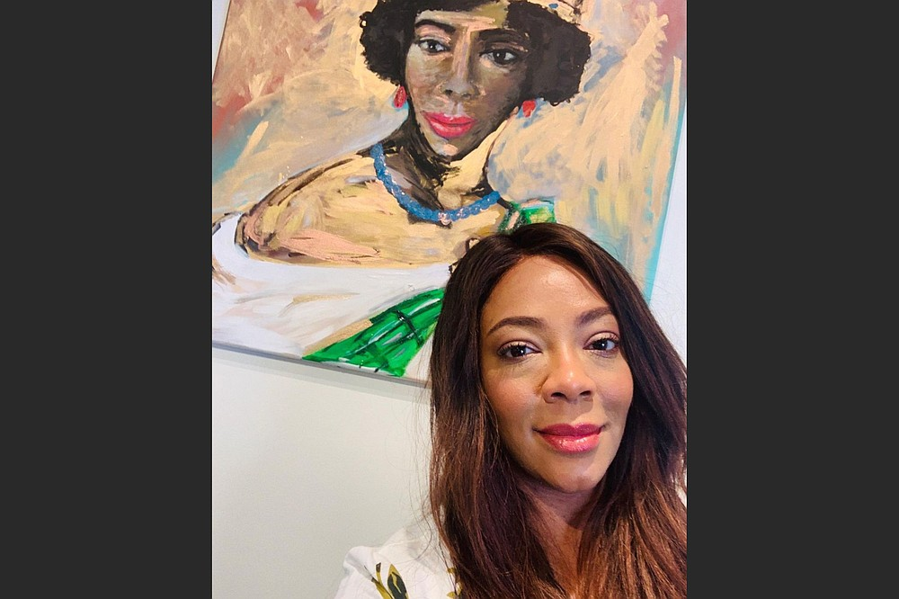 """Artist and curator Kinya Christian poses with one of her artworks on display in """"Reflections of the Black Experience,"""" at the Rogers Historical Museum through Feb. 27. (Special to the Democrat-Gazette/Kinya Christian)"""