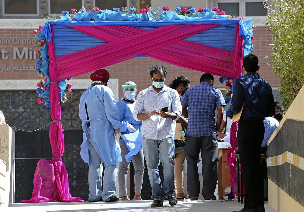 Medical staff guide visitors entering the Guru Nanak Darbar Sikh Temple, to receives their free Sinopharm covid-19 vaccine, in Dubai, United Arab Emirates, on Monday. The city's Sikh temple is administering 5,000 shots to those who may otherwise struggle to be vaccinated.