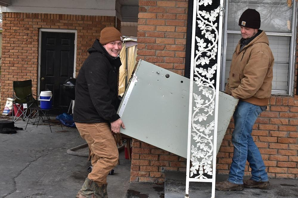 SEARK Heating and Air technicians Colton Curtis (left) and Kyle Witt carry out an old heating unit from a residence on Middle Warren Road on Friday. Both said they studied HVAC systems under their current supervisor, John Pyland, at Southeast Arkansas College.  (Pine Bluff Commercial/I.C. Murrell)