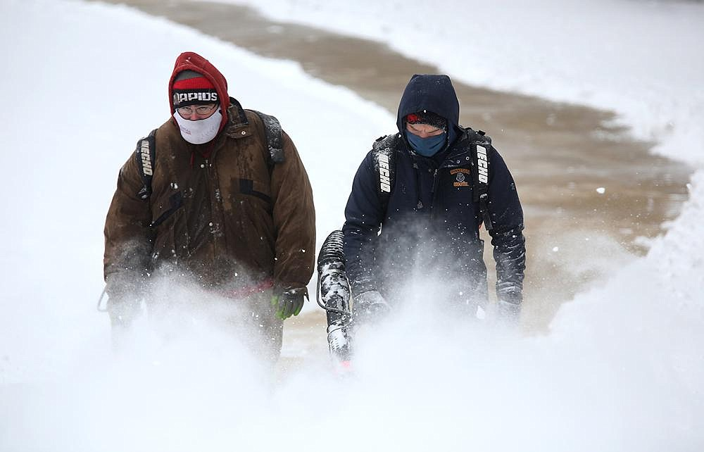 Lee Anderson (left) and Ben Hall of the University of Arkansas facilities and grounds department use leaf blowers Wednesday to remove snow from the northwest corner of Donald W. Reynolds Razorback Stadium on the Fayetteville campus.  (NWA Democrat-Gazette/David Gottschalk)