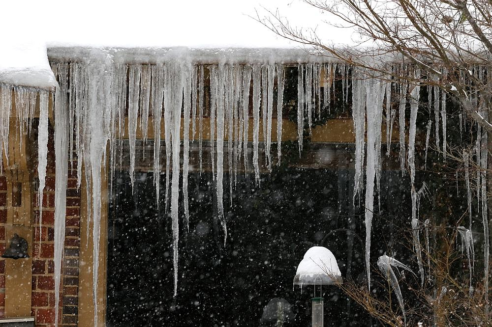 As snow picks up Wednesday, icicles hang from a house in the Hillcrest neighborhood of Little Rock. (Arkansas Democrat-Gazette/Thomas Metthe)