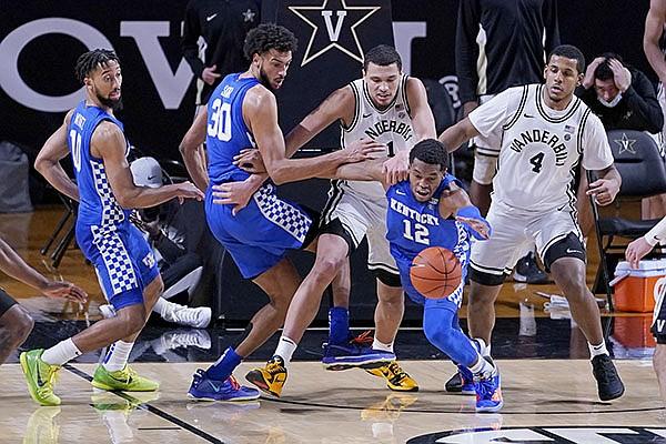 Kentucky forward Keion Brooks Jr. (12) dives for the ball ahead of Vanderbilt's Dylan Disu (1) and Jordan Wright (4) in the second half of an NCAA college basketball game Wednesday, Feb. 17, 2021, in Nashville, Tenn. Kentucky won 82-78. (AP Photo/Mark Humphrey)