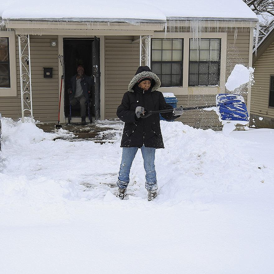 Sandy Shavers shovels her sidewalk Thursday as her husband, Daniel, watches from the doorway of their Little Rock home. The National Weather Service said Little Rock's 15-inch snow total tied a record set in 1918. More photos at arkansasonline/219snow/.