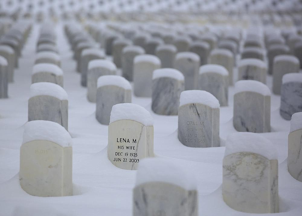 Snow sits piled up around headstones Thursday at the Little Rock National Cemetery after two snowstorms this week.